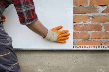 Worker placing styrofoam, polystyrene thermal insulation to brick wall, house renovation